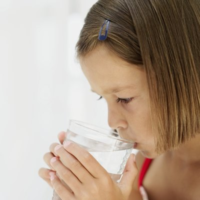 A young girl drink water while feeling ill.