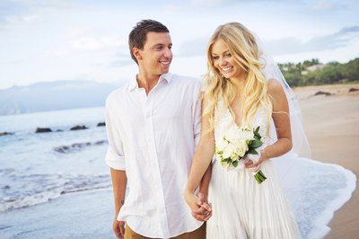 Newlywed couple walking on Caribbean beachfront