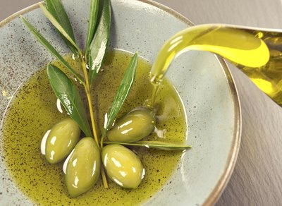 Olive oil being poured into a small bowl.