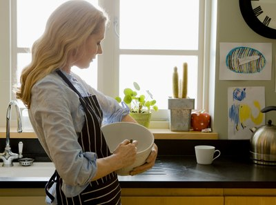 Woman using mixing bowl to crush ingredients