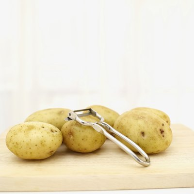 Small potatoes and peeler on cutting board.