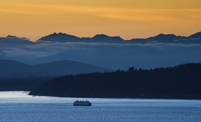Ferry passes Bainbridge Island with Olympic Mountains in the background