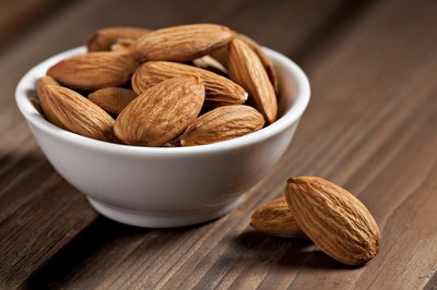 Almonds in a small bowl on a wooden table