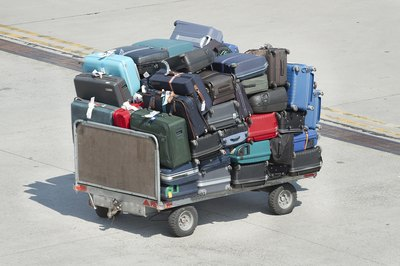 Checked bags are stacked onto a luggage cart in an airport terminal lot.