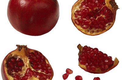 Score the sides of a pomegranate to make it easy to pull it apart into sections.