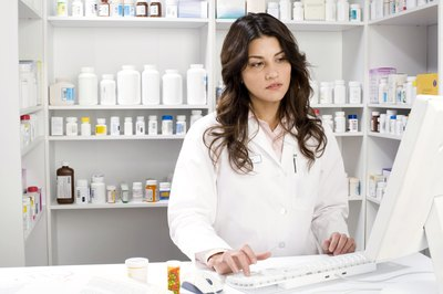 A pharmacy technician assists a pharmacist with dispensing medication.