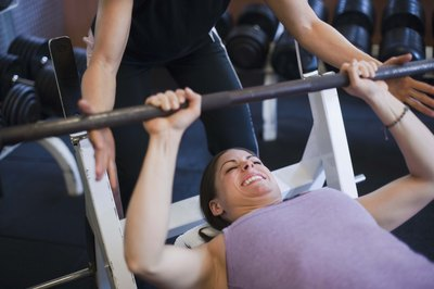 Bench press develops a woman's chest and shoulders.