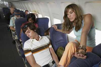 Sneak past other passengers to stretch your aching thighs on an airplane.