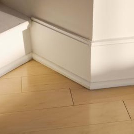 Baseboard trim can wedge in tight spots and adhere to drywall.