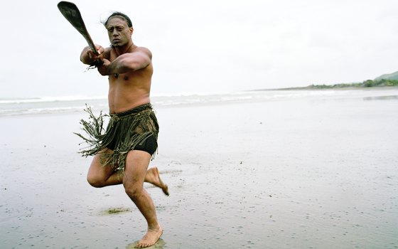 An indigenousness Maori dances on a beach.