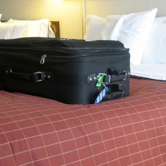 A luggage lock is placed through the two zippers on a suitcase to ensure the suitcase can't be unzipped or opened.