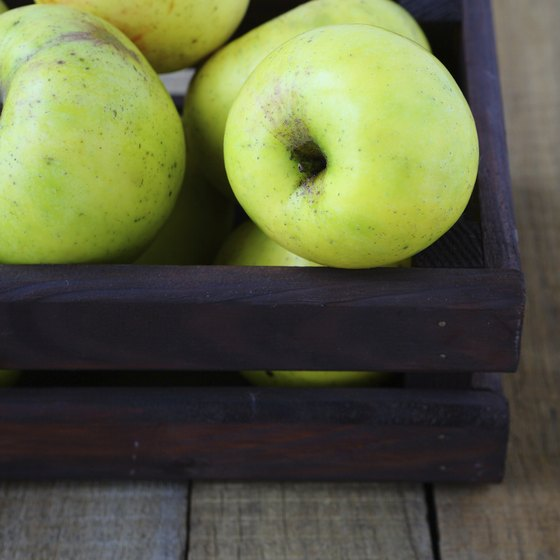 A wooden crate of golden delicious apples on a table.