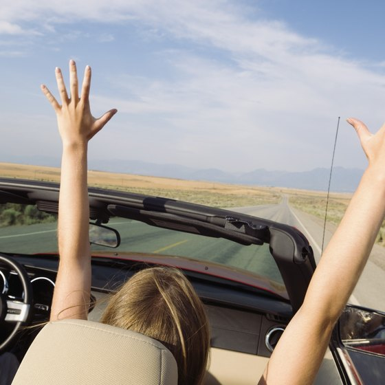 Woman with hands in her air rides in a convertible.