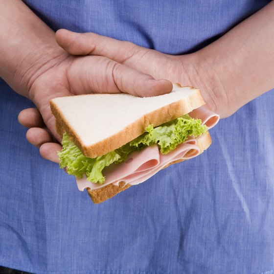 A close-up of a person hiding a sandwich behind his back.
