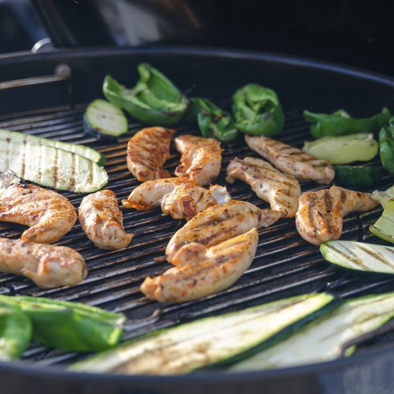 A grill with chicken and vegetables cooking.
