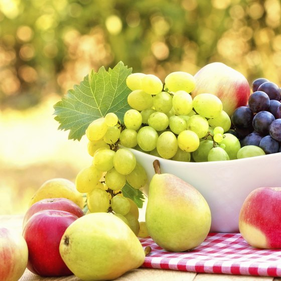 A bowl of red and green grapes on a table with fresh apples and pears