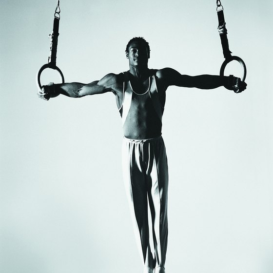 To do an iron cross, male gymnasts need extreme upper-body strength.