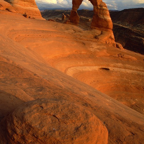 Delicate Arch perches at the edge of a giant sandstone bowl in Arches National Park.
