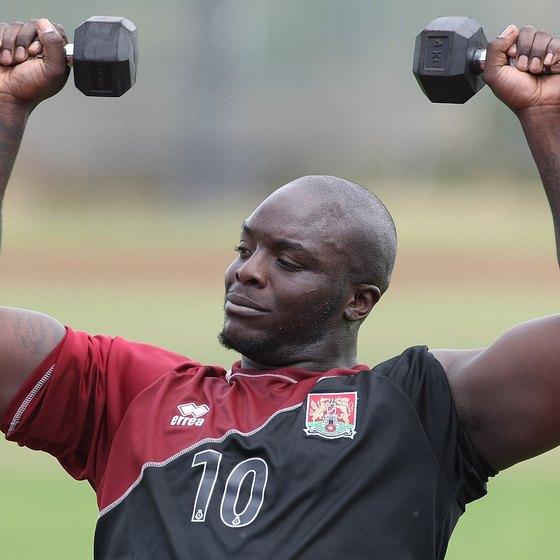Adebayo Akinfenwa of Northampton Town lifts dumbbells in a training session.