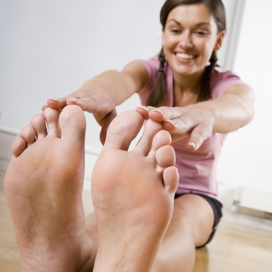 Reaching for your toes and pulling them back toward you can help stretch your soles.