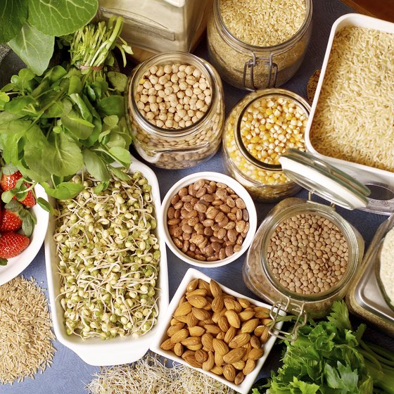 An overhead view of various types of rice, legumes, grains, fruits, vegetables and nuts.