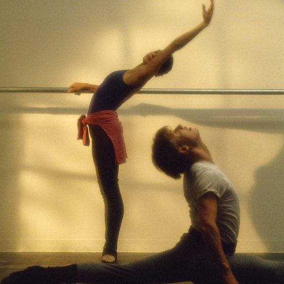 Dancers stretch using classic ballet movements.