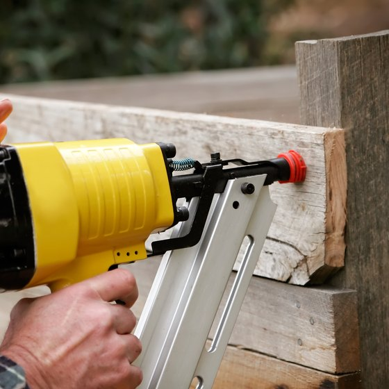 Close-up of air blow gun being used on fence construction