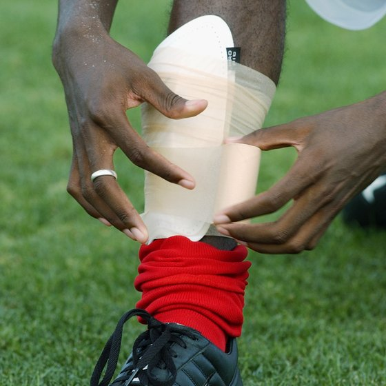 Damarcus Beasley of the Chicago Fire adjusts his shin guard.