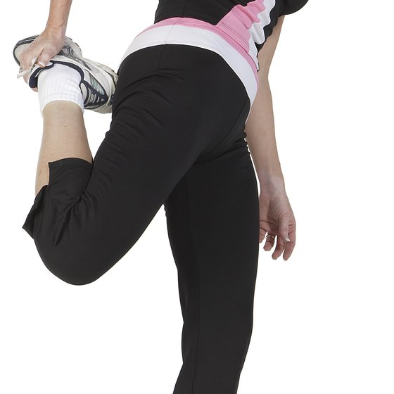 A woman performs a safe quad stretch.