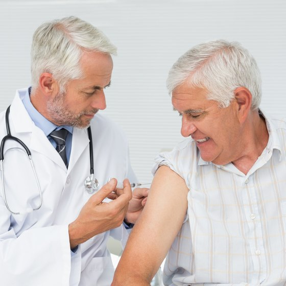 Mature man getting an injection in his arm.