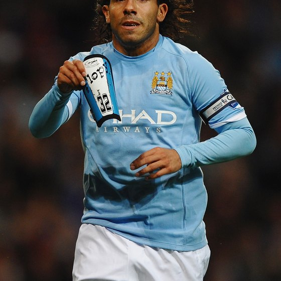 Carlos Tevez of Manchester City holds up a shin guard without ankle protectors.