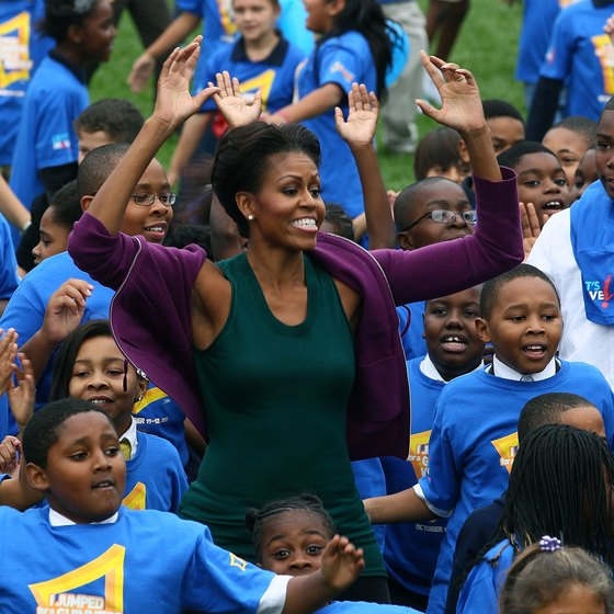 First Lady Michelle Obama performing jumping jacks with a group of school children.