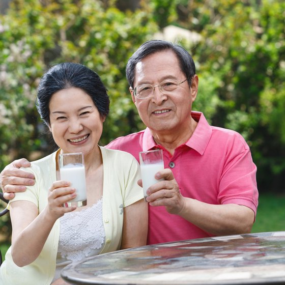 A mature couple drinking a glass of milk.