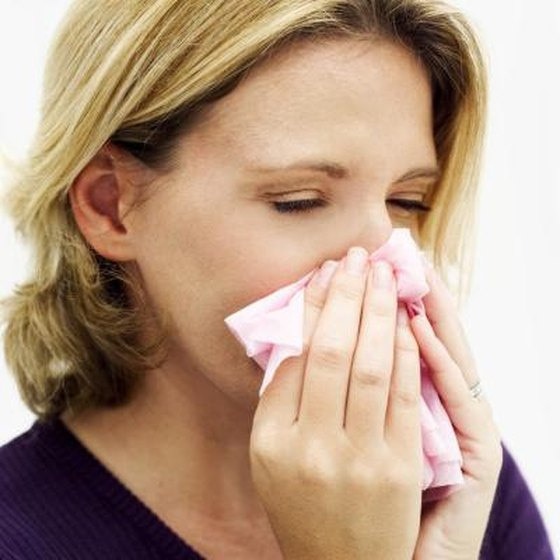 A woman blows her nose with a tissue.