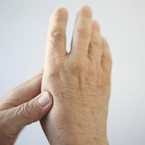 An older woman expieriences arthritis pain in her hand.