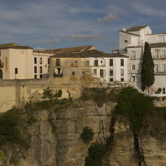 The white-washed houses in Ronda cling to its craggy limestone cliff face.