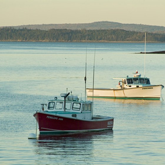Fishing boats rest in a harbor in Maine.