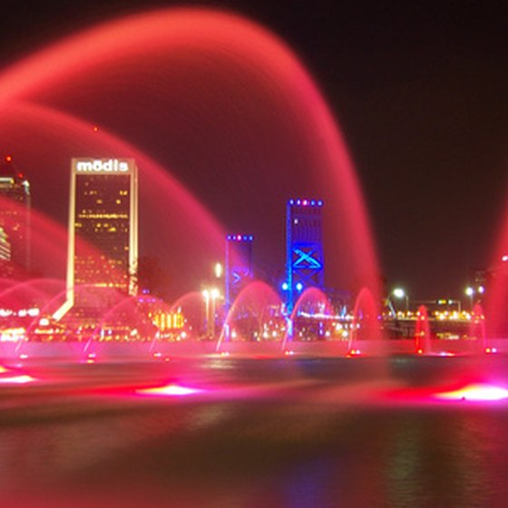 An illuminated fountain and the Jacksonville skyline at night