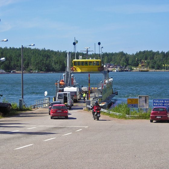Cars driving onto a ferry.