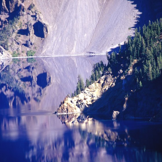 Phantom Ship rises through the reflection of hillsides surrounding Crater Lake.