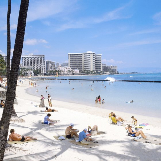 Waikiki's calm water and white sand attracts snorkelers and parasailors to its shore.