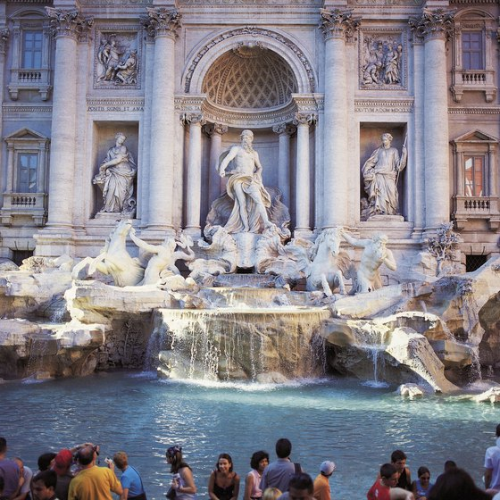 Visitors toss a coin in the Trevi Fountain, hoping to return to Rome again.