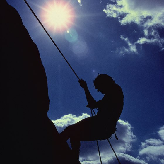 A climber rappels down a cliff face.