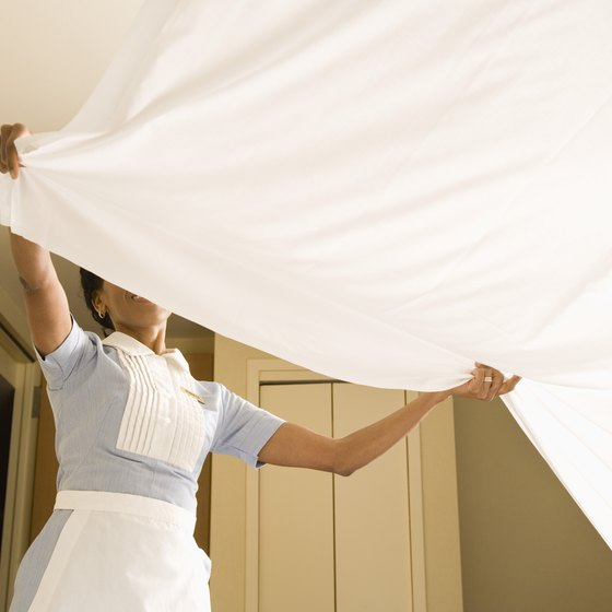 Making the bed is one of a hotel room attendant's duties.