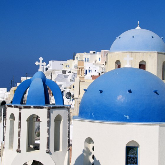 The blue-capped Santorini skyline towers over the surrounding Aegean Sea.