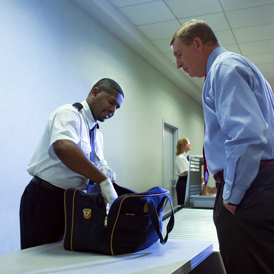 TSA officials physically inspect luggage at the airport for added security.
