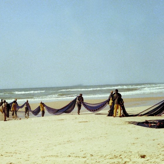Locals wield fishing nets on a beach in Senegal.