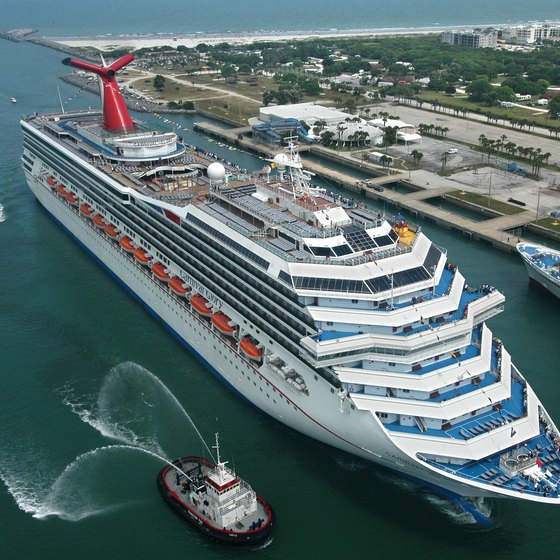 A Carnival Cruise ship receives a tugboat escort in the Port of Miami.