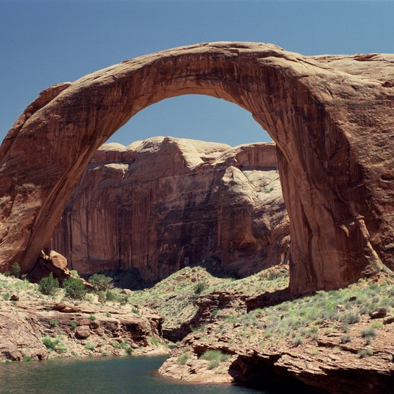 Rainbow Bridge National Monument soars into the sky by the shores of Lake Powell.