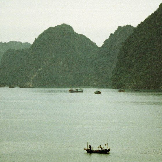 Vessels dock close to the cliffs along the waters of Halong Bay.